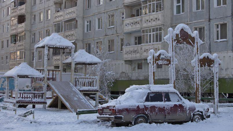 A car covered in ice is pictured near a playground in Yakutsk