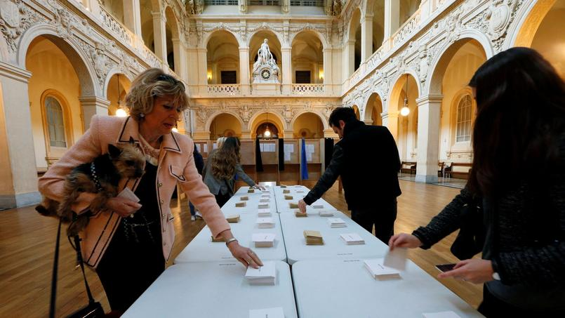 People choose their ballots before voting in the first round of 2017 French presidential election at a polling station in Lyon