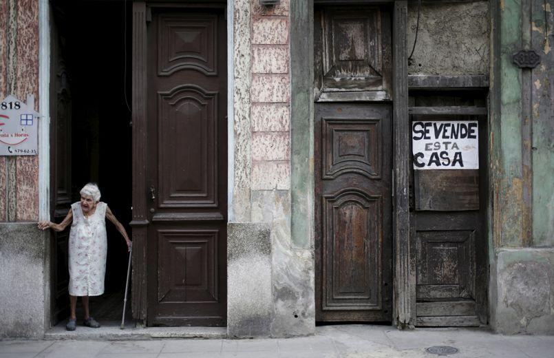 An old woman stands near a house for sale in Havana