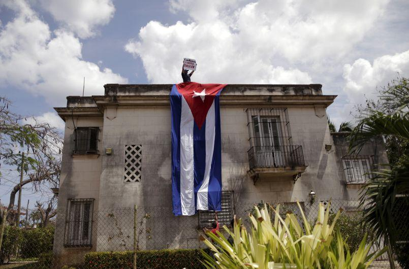 A government supporter holds a sign as he stand atop a building during a protest against a regular march by the 'Ladies in White' dissident group in Havana