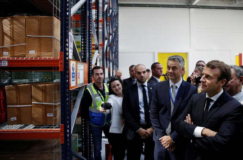 French President Emmanuel Macron stands near Amazon France Director Frederic Duval during a visit at the Amazon factory in Boves