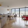 Une pièce à vivre très éclairée grâce aux baies vitrées qui offrent une vue sur la colline.
