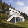 Une façade avec des bardages métalliques pour cette maison sous la colline.