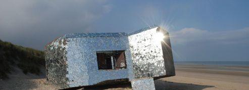 Sur la plage, un blockhaus recouvert d'éclats de miroirs