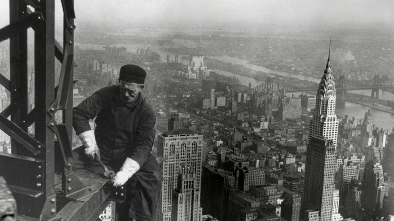Un ouvrier assis sur une poutre métallique sur le chantier de construction de l'Empire State Building à Manhattan, 1930.