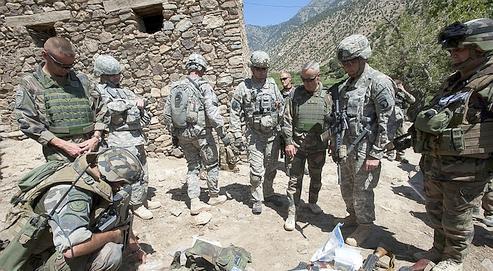 Le 22 août 2010, le général Chavancy (tête nue au centre) avec ses chefs de bataillon français et américain, dans la vallée d'Uzbin. Devant lui, une saisie d'armes, de munitions et de drogue.
