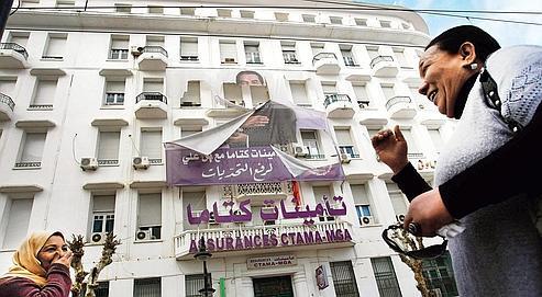 Deux femmes rient devant un portrait déchiré de l'ancien président Ben Ali, dimanche, dans le centre de Tunis.