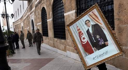 Un employé des services du premier ministre transporte, dans une rue de Tunis, un tableau de l'ex-président tunisien après l'avoir décroché.