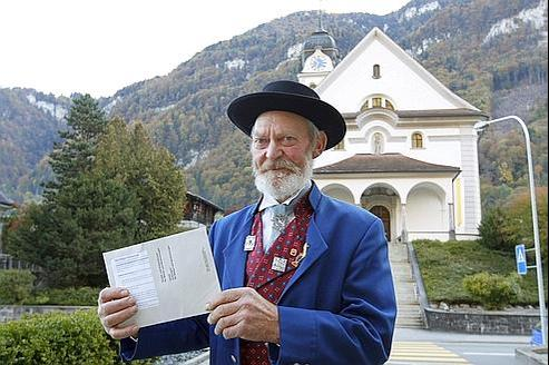 Un citoyen suisse exhibe sa carte électorale, dimanche à Wolfenschiessen, dans le canton de Nidwald.
