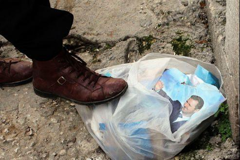 Portrait de Bachar el-Assad déchiré par un rebelle. Les biens de la Syrie sont majoritairement aux mains d'une petite élite corrompue.