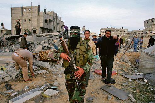 Un milicien du Hamas patrouille sur les lieux d'un bombardement à Rafah