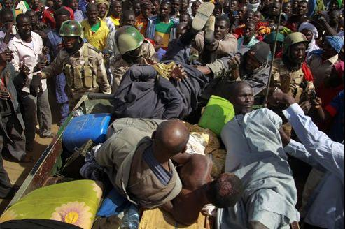 Des soldats maliens protègent de la foule des islamistes présumés arrêtés lundi à Gao par des miliciens.