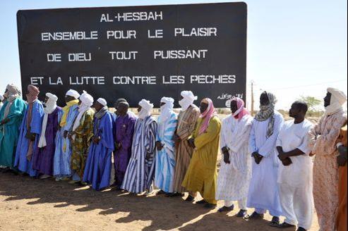 Des Maliens s'apprêtent, mercredi à Gao, à effacer un panneau dressé par des islamistes liés à Aqmi avant leur départ de la ville.