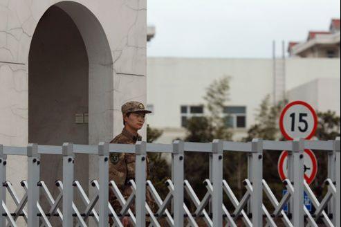 Un soldat monte la garde devant le bâtiment qui abrite l'unité 61398, mardi, dans la banlieue de Shanghaï.
