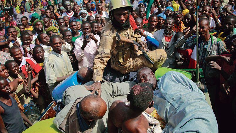 Un soldat malien surveille des prisonniers soupçonnés d'être des islamistes extrémistes, le 29 janvier, à Gao.