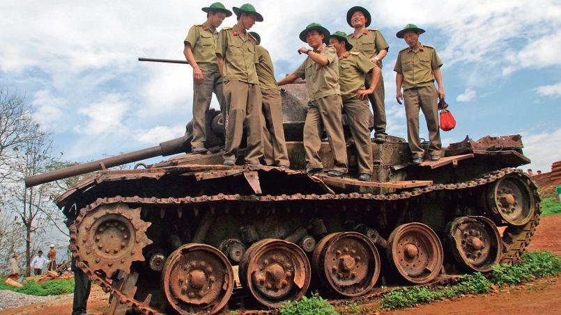 Des soldats vietnamiens sur les débris d'un char français en 2004 sur une colline de Diên Biên Phu.