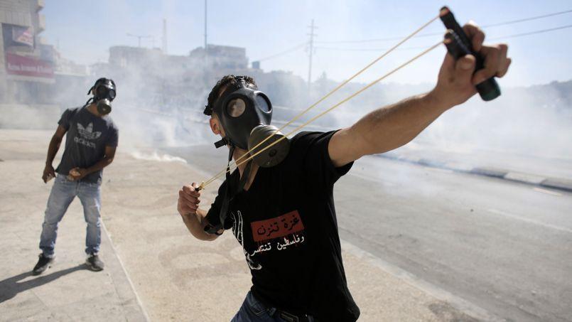 Des manifestants palestiniens protestent, en jetant des pierres.