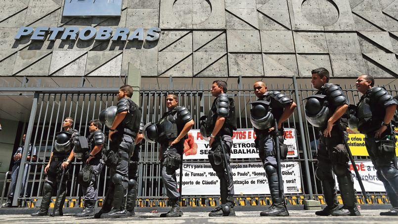 Des policiers sécurisent les accès du siège de Petrobas à Rio, pendant une manifestation des métallurgistes, mercredi.