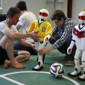 Employees of the Institute for Computer Science prepare humanoid robots dressed in the colours of Germany's and Brazil's