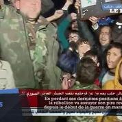 Des Syriens pro el-Assad célèbrent la victoire d'Alep devant la télévision syrienne