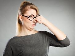 Une femme se pince le nez en raison de l'atmosphère malodorante