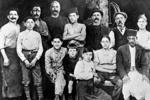Albert, à 7 ans (au centre en noir), entouré de sa famille, dans un atelier de tonnellerie. Crédit photo: Rue des Archives/PVDE