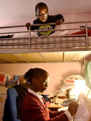 Bintou, 7ans, a gardé son uniforme pour faire ses devoirs chez elle, sous le regard attentif de son petit frère.
