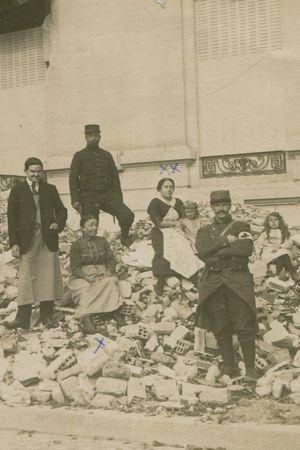 La famille Peiffer-Weber devant les débris de leur maison, à Reims, en 1918. Au milieu, assises sur les débris, Mme Peiffer et ses deux filles, Juliette et Elisa, qui ont confié cette image à Europeana.