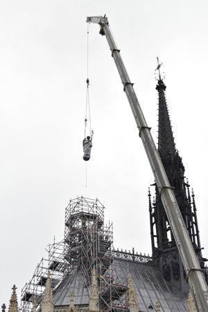 La statue de saint Michel restaurée a été replacée au sommet de la Sainte-Chapelle.