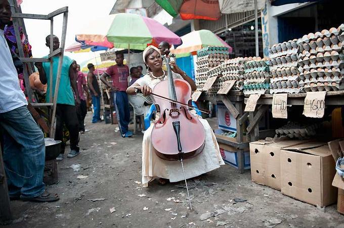 Le visage radieux, illuminé par les notes qui s'évadent de son violoncelle, Joséphine Msimba-Mpongo fait partie de l'orchestre depuis sa création. Ici, elle joue au marché central de Kinshasa, où, pour gagner sa vie, elle vend des oeufs et propose aussi des omelettes.
