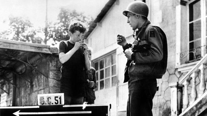 <b>CHEWING-GUM </b>- Ici, un GI américain qui apprend à un enfant francais à mâcher du chewing gum. Avant la Libération, les Français mâchent peu de chewing-gums mais l'arrivée des soldats américains armés de leurs paquets de pâtes à mâcher va changer durablement les habitudes dans l'Hexagone. Si la marque Wrigley fondée en 1891 fournissait les combattants, c'est surtout Hollywood qui va séduire les Français. Le produit a été lancé en France en 1952 par le GI Américain, Courtland E. Parfet, ayant participé au débarquement en 1944 en Normandie. Aujourd'hui, les Français sont les deuxièmes consommateurs de chewing-gum au monde, derrière les Américains.