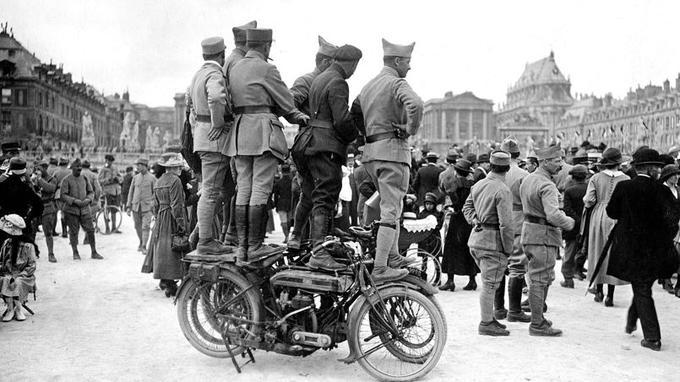 Des soldats montent sur leur motocyclette pour assister à l'arrivée des délégations au Château de Versailles le 28 juin 1919.