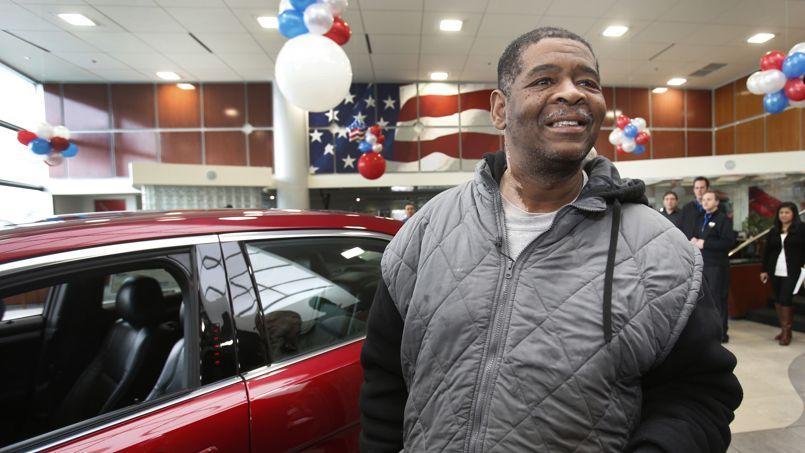 James Robertson, le 6 février 2015 à côté de la voiture qui lui a été offerte pour qu'il puisse se rendre à son travail.