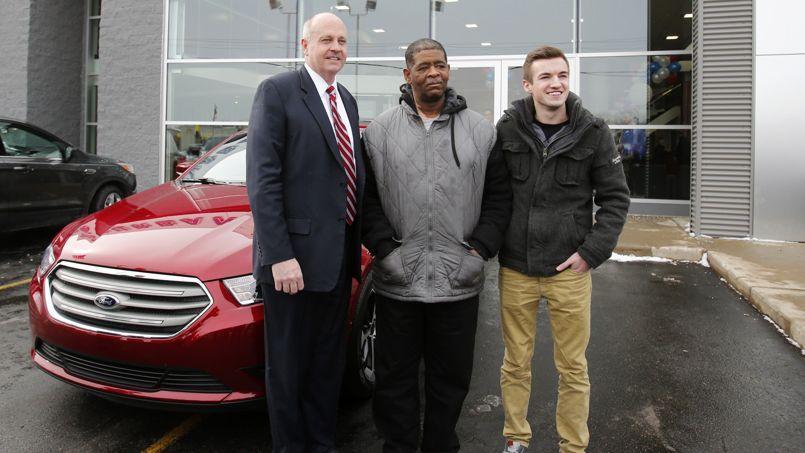 James Robertson pose le 6 février 2015 avec le banquier Blake Pollock à sa gauche et l'étudiant Evan Leedy (à sa droite) qui a monté la collecte, devant la voiture qui lui a été offerte par une concession Ford de l'agglomération de Detroit.