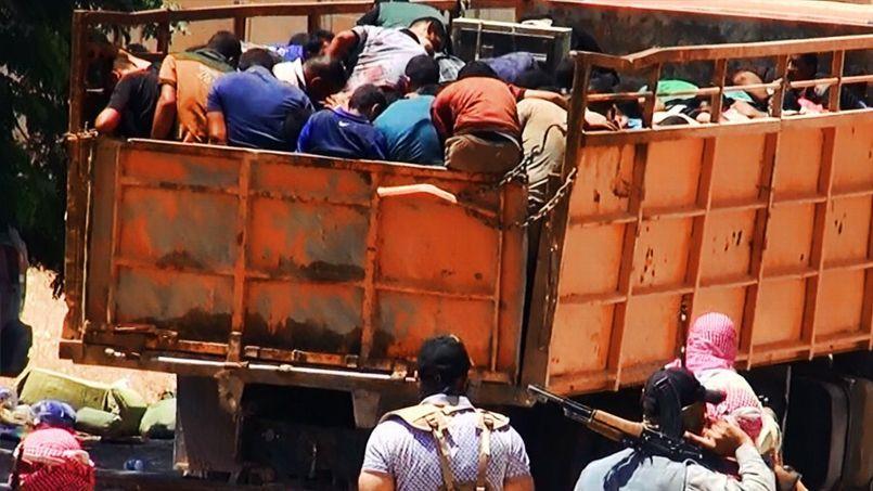 Les prisonniers sont embarqués à l'arrière d'un camion encadré par des militants de l'EIIL.