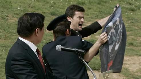 Un activiste perturbe le discours du président du comité d'organisation des Jeux de Pékin, Liu Qi, lundi à Athènes . (AP).