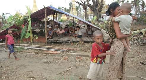 Une mère et ses enfants devant un refuge précaire, près de Bogalay.