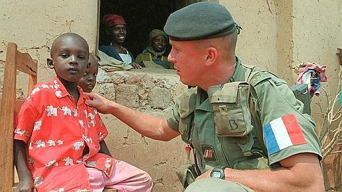Un soldat français discute avec un jeune Rwandais, en juillet 1994, dans l'est du pays.