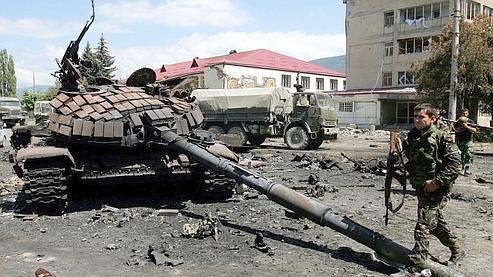 Un soldat ossète passe devant un char géorgien, détruit dans les combats qui ont touché la ville de Tskhinvali.