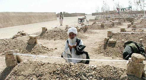Un homme se recueille sur la tombe de l'une des victimes du bombardement américain, samedi à Azizabad.