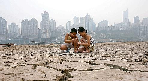 Des enfants jouent sur une portion asséchée de ma rivière Jialing, en 2006 à Chongqinq. La Chine doit faire face à la raréfaction et à la pollution de l'eau.
