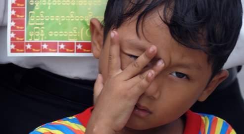 Un enfant pose devant le portrait de Aung San Suu Kyi, hier à Bangkok, lors d'une manifestation de soutien à l'opposante birmane.