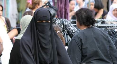 Une jeune musulmane portant la burqa traditionnelle dans une rue de Vénissieux, en banlieue lyonnaise.
