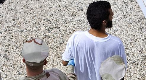 Deux gardiens escortent un prisonnier à Guantanamo, le 18 novembre dernier. Selon le Pentagone, la prison, après avoir hébergé jusqu'à 800 détenus, en compte encore 229, originaires d'une trentaine de pays.