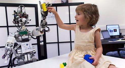 iCub et Olympe, 4 ans, échangent des Lego. C'est la toute première rencontre du robot avec un enfant. Peter Ford Dominey, chef de projet à l'Inserm, est visiblement rassuré par ce premier contact entre la petite fille et l'androïde. Le chercheur redoutait qu'Olympe soit effrayée par l'aspect d'iCub, qui n'est pas équipé ici du «masque» qui luidonnera un visage humain. La fillette n'a eu aucune hésitation. Peutêtre le considère-t-elle comme un jouet ?
