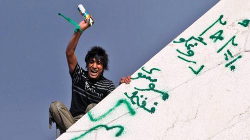 Un partisan de l'opposant Moussavi peint des slogans sur la Tour de la Liberté, à Téhéran. Pour Nicolas Baverez, «la révolution iranienne comporte peut-être une dimension historique, en marquant la première pierre d'une réconciliation possible de l'islam avec la modernité et la liberté». (Crédits photo : AP)