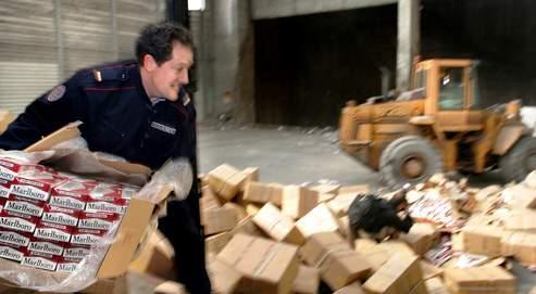 Un douanier décharge d'un camion, le 21 mars 2005 à Ludres, des cigarettes de contrebande saisies par les douanes de Nancy.