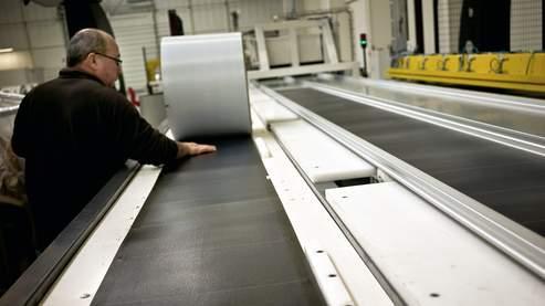 Un employé de l'entreprise de constructions métalliques Ravoyard SA pose une membrane photovoltaïque.