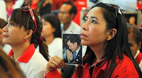 Une partisane de l'ancien premier ministre Thaksin Shinawatra, exilé à Dubaï, tient son portrait, vendredi, à Bangkok, en signe de protestation contre les mesures prises à son encontre par la Cour suprême.
