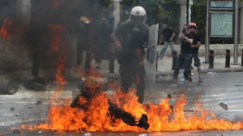 Un policier anti-émeute pris dans les flammes de l'explosion d'un cocktail molotov, à Athènes.
